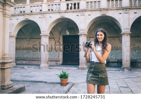 Half length portrait of cheerful brunette woman in casual wear holding camera making photos during trip vacations, smiling female amateur enjoying spending free time on hobby taking pictures