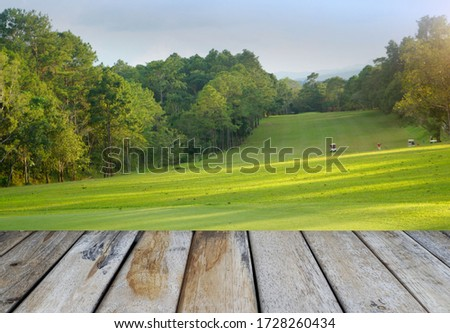 Wooden floor and golf course background. Fresh spring green golf course with wood floor. Beauty natural background, Empty wooden deck table with Green background.