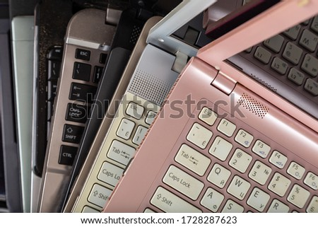Stack of used laptops in different colors and models. Tha notebooks for repair and service. Royalty-Free Stock Photo #1728287623