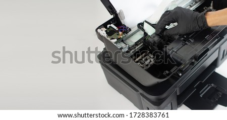 Printer repairman inspecting printer interior.Copy space. Concept of professional printer maintenance Technical assistance in office hardware Continuous repair of the ink system. Printer problems .. #1728383761