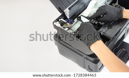 Printer repairman inspecting printer interior.Copy space. Concept of professional printer maintenance Technical assistance in office hardware Continuous repair of the ink system. Printer problems .. #1728384463