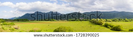 Panorama landscape of southern Lika in spring. Grassy fields and Crnopac and Velebit mountains #1728390025
