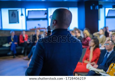 Male presenter speaks to audiences at seminar Royalty-Free Stock Photo #1728406219