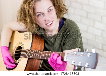 A young teenage girl smiles and plays the guitar in rubber gloves and learns chords or a song. Getting out of quarantine. Fastidiousness. Misophobia #1728413503