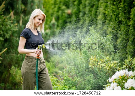 blonde girl watering her garden in summer #1728450712