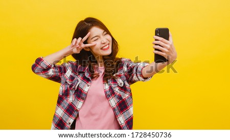 Smiling adorable Asian female making selfie photo on smartphone with positive expression in casual clothing and looking at camera over yellow background. Happy adorable glad woman rejoices success. #1728450736