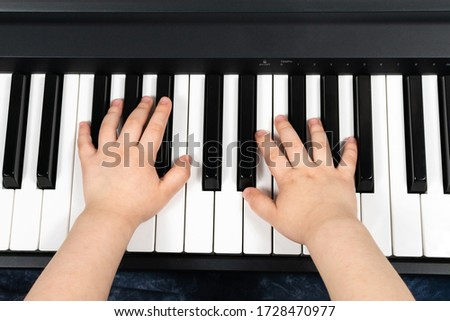 Hands of a young child playing the piano. Learning to play the piano. Studying at home. To stay home. View from above. Royalty-Free Stock Photo #1728470977