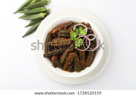 Bhindi kurkure or crunchy okra or ladies' fingers, a Rajasthani traditional dish served in a white ceramic bowl  along with raw bhindi aside
