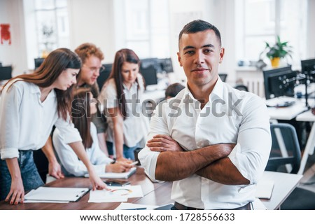 Young male employee in formal clothes standing in the office. Group of people working behind. Royalty-Free Stock Photo #1728556633