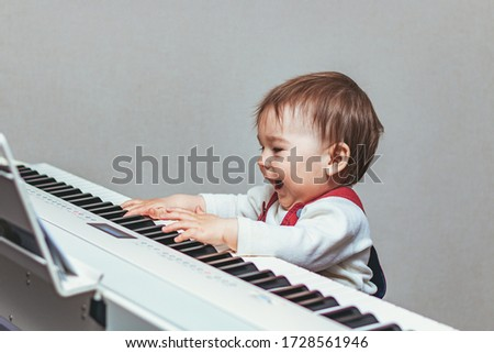 Small child, toddler, having fun and playing electric piano