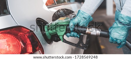 woman filling up petrol into her new car. price of petrol lower down during epidemic. Consumer filling car at petrol station. Petrol and diesel filling up station. woman wearing gloves whilst filling #1728569248