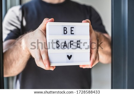 Healthcare and Safety concept. Unrecognised man holding lightbox with text Be safe during coronavirus COVID-19 pandemics #1728588433