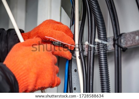 Hands with gloves fasten the cable ties on the cable, which are on the cable tray. Close-up. Horizontal orientation. Royalty-Free Stock Photo #1728588634