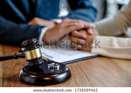 Judge gavel and two golden marriage ring, Contract decree of divorce (dissolution or cancellation) of marriage, husband and wife during divorce process and signing of divorce contract. #1728589462