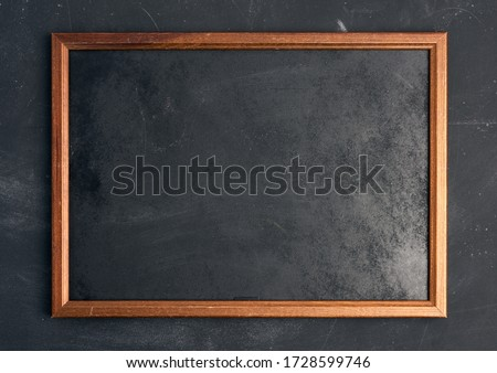 empty wooden chalk board on a black background, place for an inscription Royalty-Free Stock Photo #1728599746
