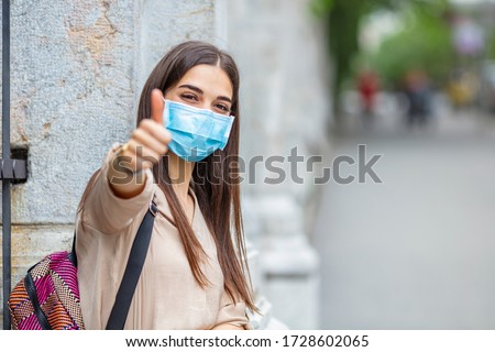 Woman doing thumbs up gesture wearing a protective mask. Young woman in medical sterile protective mask on her face, walking in a European city, showing thumbs up #1728602065