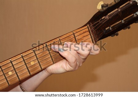 A woman's hand with a manicure holds a chord on a guitar. The girl plays the guitar. Fingerboard and frets. #1728613999