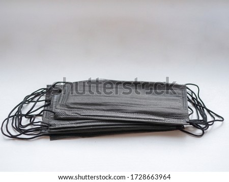 bundle of black surgical mask with rubber ear straps. Typical three-layer surgical mask for covering mouth and nose. (Clipping path). Protection concept
