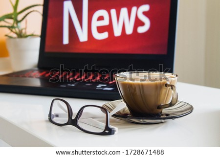 Red word news on the laptop screen. Glasses and a Cup of coffee are on the white table. #1728671488