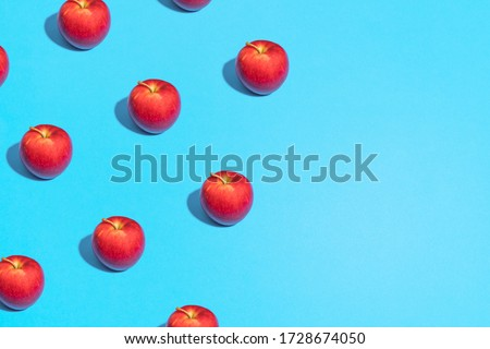 red Apple pattern on bright light blue background. Minimal flat lay food texture. Summer abstract trendy fresh concept.