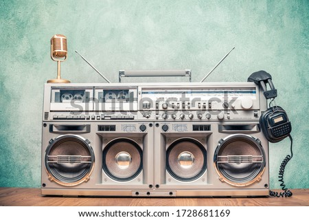 Retro old ghetto blaster stereo radio cassette tape recorder boombox from circa 80s, golden microphone, headphones front concrete wall background. Nostalgic music concept. Vintage style filtered photo