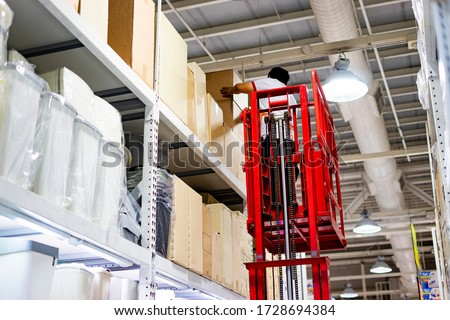 retailer warehouse stock of produce food and products, worker employee man upon human lifter machine checking item and products restocking and replacing, with big cardboard box stacking a high shelf