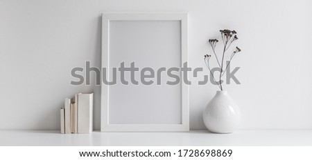 White desk with photo frame, office supplies, boxes and fresh natural leaf in design vase.