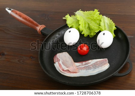funny picture with chicken eggs and bacon on the pan in the form of emoji