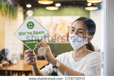 Business owner Asian woman wear protective face mask ppe hanging open sign at her restaurant / café, open again after lock down due to outbreak of coronavirus covid-19 #1728718951