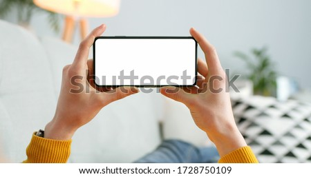 Close up of horizontal black smartphone with blank screen in woman hands. Mobile phone with blank copy space screen for your text Royalty-Free Stock Photo #1728750109