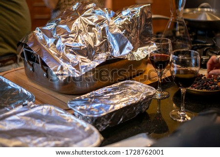 Various food dishes covered in tin foil at a party or Thanksgiving #1728762001