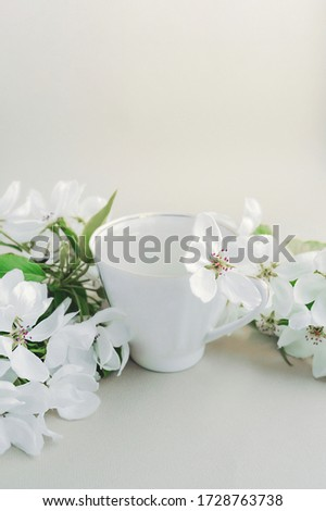 White porcelain cup with green tea and a fresh white pear tree flower in a lush bouquet of blooming white flowers and green bright leaves on a twig on a light table. vertical image