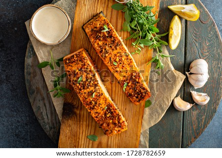 Cedar plank grilled or roasted salmon with herbs, garlic and spices Royalty-Free Stock Photo #1728782659