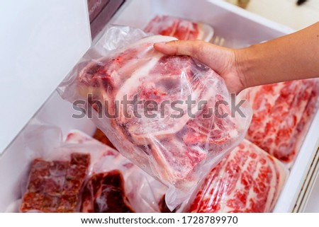 Closeup of hand choosing fresh raw ribs meat in the freezer Royalty-Free Stock Photo #1728789970