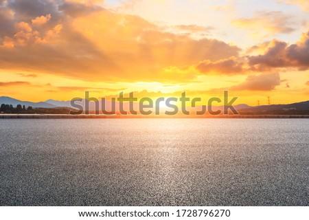 Asphalt road ground and mountain landscape at sunset.