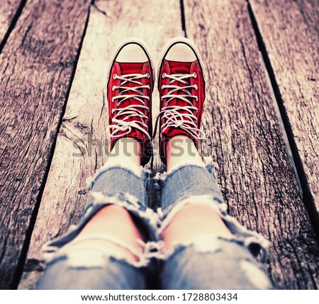 Red sneakers on wooden white floor background, top view. Conceptual image of a dancing couple, youth, dance floor. Casual and lifestyle concept