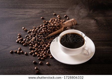 Coffee beans and hot coffee on the table #1728806332