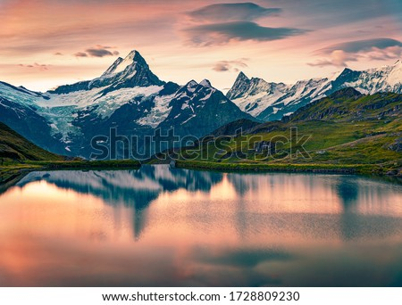 Breathtaking summer sunrise on Bachalpsee lake with Schreckhorn and Wetterhorn peaks on background. Astonishing morning scene in the Swiss Bernese Alps, Switzerland, Europe.  Royalty-Free Stock Photo #1728809230