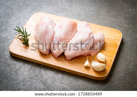 fresh raw middle chicken wings on wooden board with ingredients Royalty-Free Stock Photo #1728850489