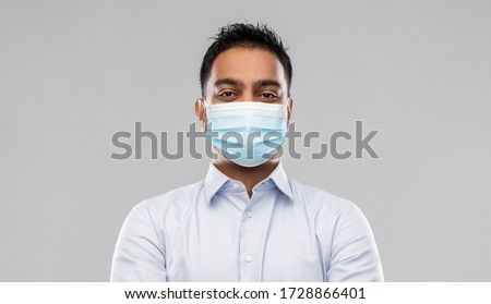 business, healthcare and people concept - portrait of indian man in shirt wearing face medical mask for protection from virus disease over grey background Royalty-Free Stock Photo #1728866401