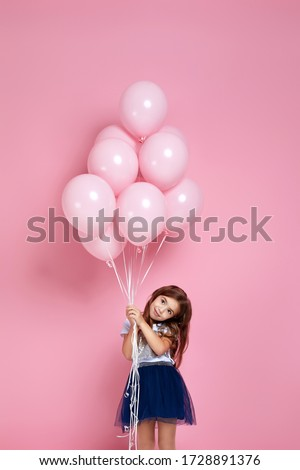 Smiling adorable little child girl posing with pastel pink air balloons isolated over pink background. Beautiful happy kid on a birthday party.