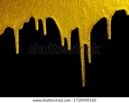 Golden paint dripping liquid paint, isolated on black background. Flowing abstract Gold metallic paint drops close-up. Leaking.gold paint dripping or flowing on black background  Royalty-Free Stock Photo #1728900160