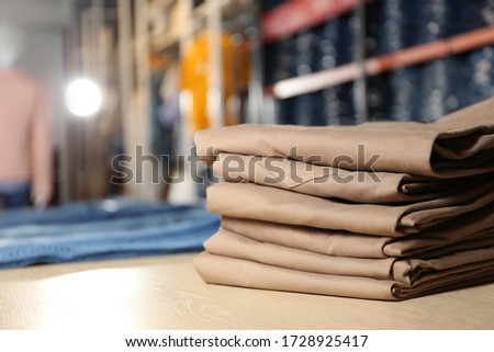 Stack of brown jeans on display in shop #1728925417