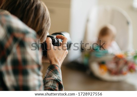 Newborn hotographer takes picture of kid on profeshional camera. Fun, happiness, party, guests, celebration, family anniversary. Usual moments of everyday life. Casual, lifestyle. Childhood.