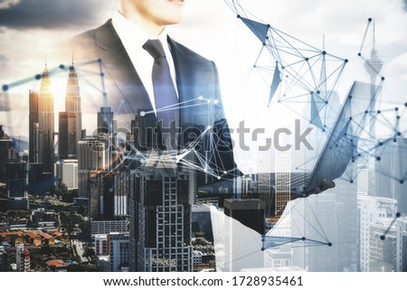 Businessman using laptop with creative polygonal hologram on city view background. Communication and teamwork concept. Multiexposure