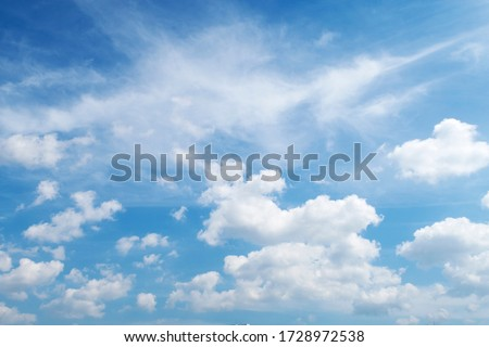 Natural sunny blue sky background with beautiful puffy white cumulus clouds & fluffy cirrus cloudscape on bright daylight horizon in tropical summer sunlight & exotic sun ray at sunny & sunshine day #1728972538