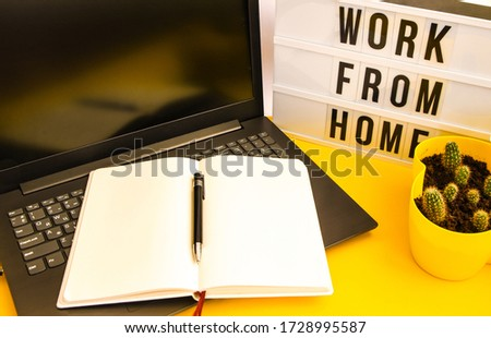 Text WORK FROM HOME with notebook, laptop and pen, cactus, work from home place, freelance environment on yellow background copy space, planning day, to do list #1728995587