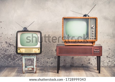 Two old retro classic analog CRT TV set receivers and aged wooden television stand with outdated amplifier front aged concrete wall background. Broadcasting, news concept. Vintage style filtered photo Royalty-Free Stock Photo #1728999343