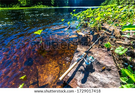 Fishing rod at summer river water. Fishing rod view #1729017418