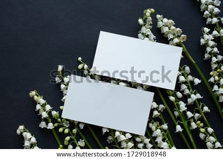 Mockup with business card lily of the valley on black table. background with copy place